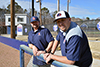 Two young coaches lean on the fence of a baseball field and smile