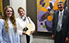 One young woman, another woman and a man stand and pose in front of an abstract painting on the wall.