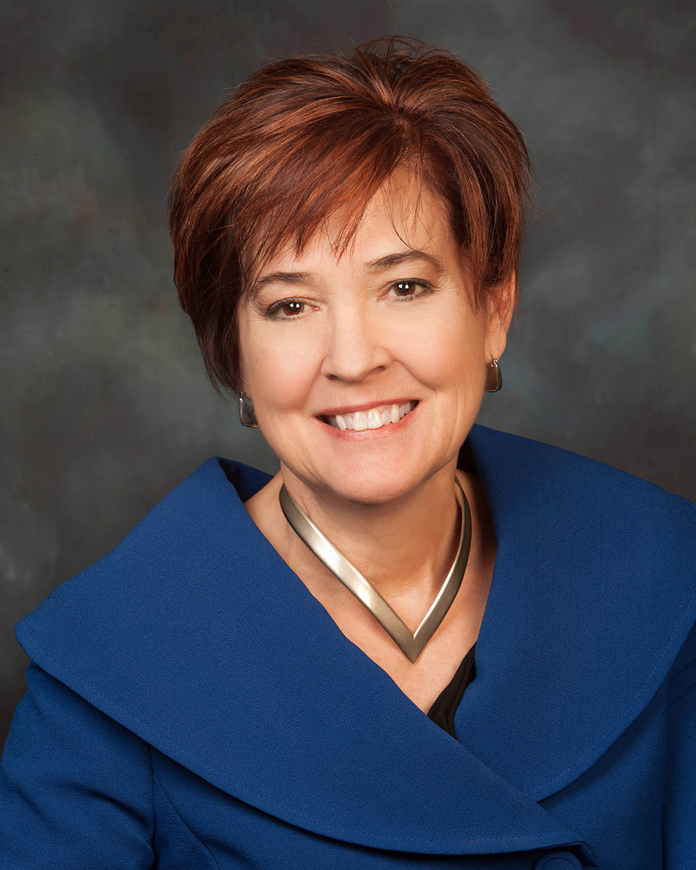 A portrait of Bonnie Suderman, a smiling woman with short brown hair, wearing a blue jacket.